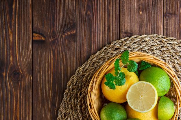 Лаймы с лимонами, зеленью в плетеной корзине на деревянном столе