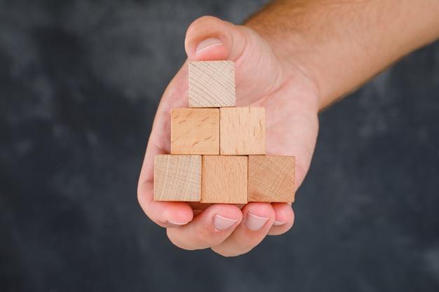 汚れた灰色のテーブルの側面図のビジネスコンセプト。木製のブロックを持っている手。