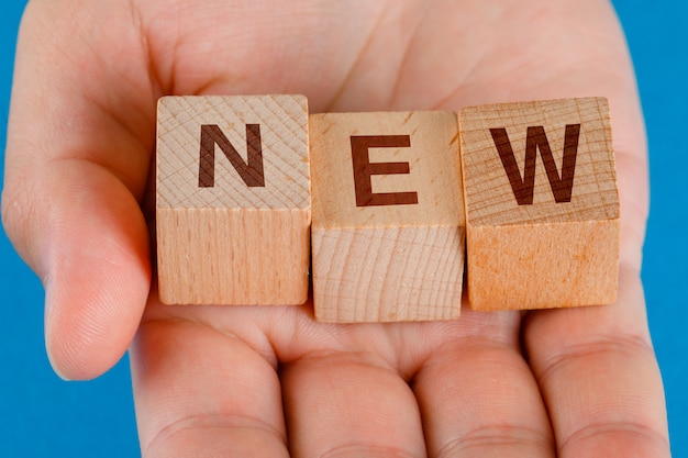 青いテーブルのクローズアップのビジネスアイデアのコンセプト。新しい単語を持つ木製キューブを持っている手。