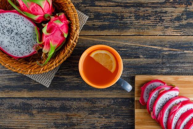 まな板とバスケットのドラゴンフルーツ、木製のテーブルに平らなお茶を置く