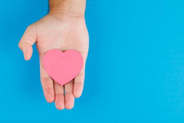 Концепция отношения на синем столе плоской планировки. рука держит сердце бумаги