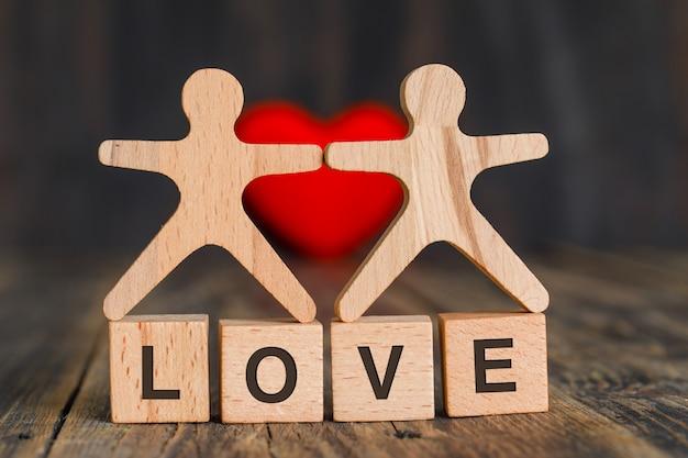 Концепция отношения с красным сердцем, деревянными кубиками и человеческими моделями на взгляде со стороны деревянного стола.