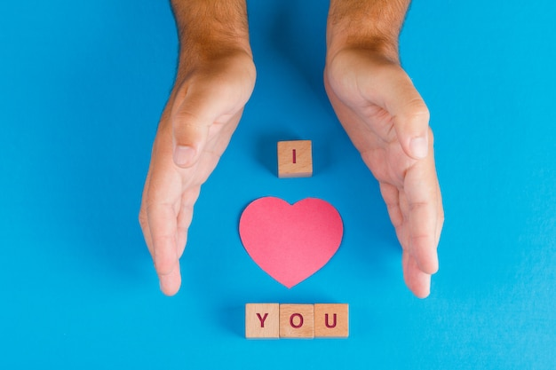 青いテーブルフラットの木製キューブとの関係の概念を置きます。紙を保護する手は心を切った。