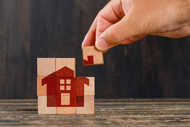 木製のテーブルの側面図で家のコンセプトにとどまります。木製キューブを持っている手。