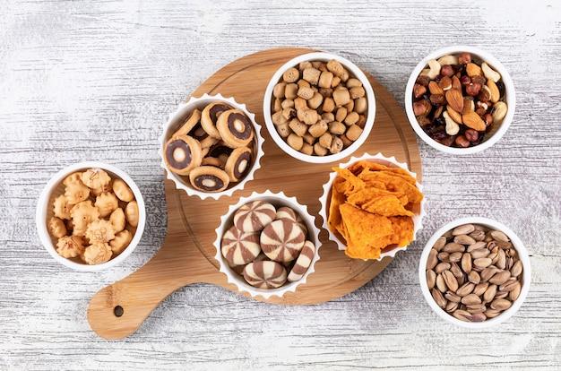 Вид сверху различных видов закусок, как орехи, крекеры и печенье в мисках на деревянной разделочной доске на белой горизонтальной поверхности