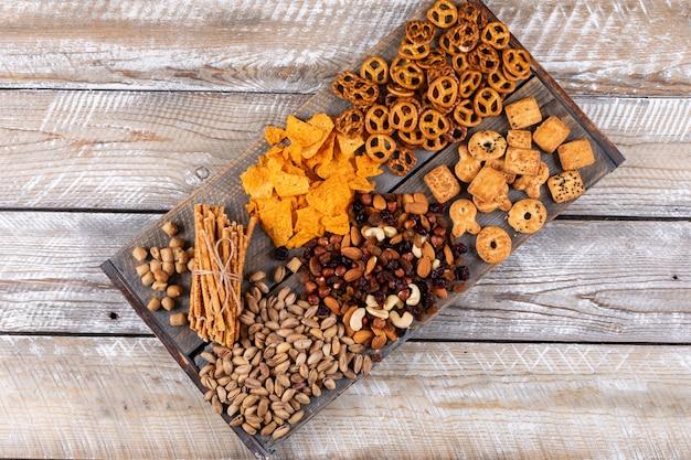 白い木製の表面の水平にナッツ、クラッカー、クッキーとしてスナックの異なる種類のトップビュー