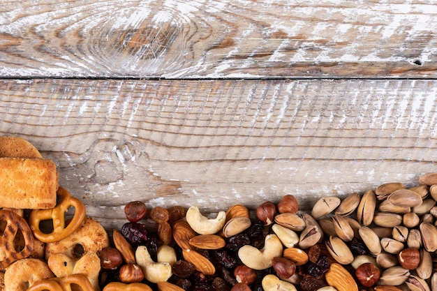 水平方向の白い木製の背景にコピースペースを持つナッツ、クラッカー、クッキーとしてスナックの異なる種類のトップビュー