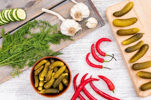 トップビューキュウリのピクルスと新鮮な唐辛子ニンニクとディルホワイト木製