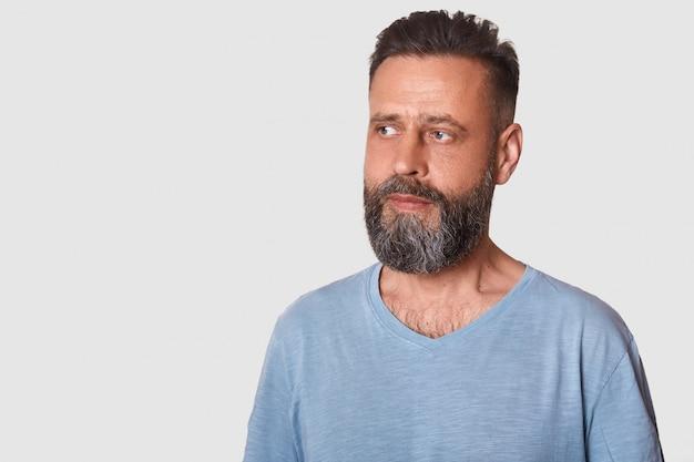 Студийный снимок привлекательного шведского парня со стильным стрижкой и бородой в серой футболке, выглядит задумчиво