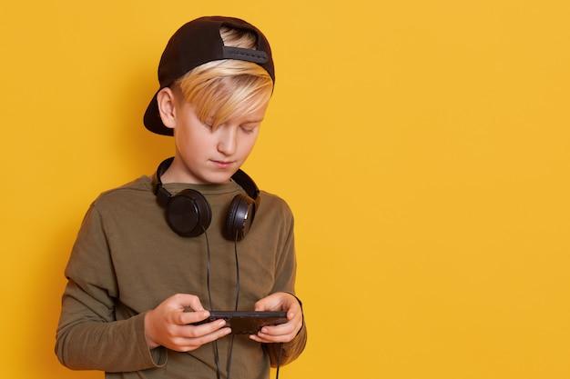 首にヘッドフォンをつけた少年、ジュニパーグリーンのシャツと黒のバイザーキャップを身に着けている小さな男の写真