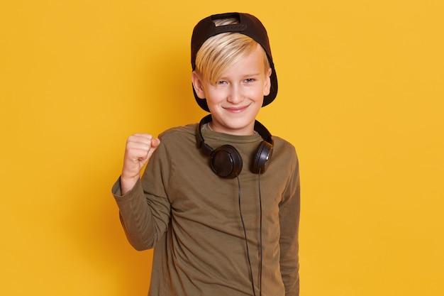 緑のセーターと後方帽子、上げられた手で立って、奇抜な表情を持つ少年のポートレートを閉じます
