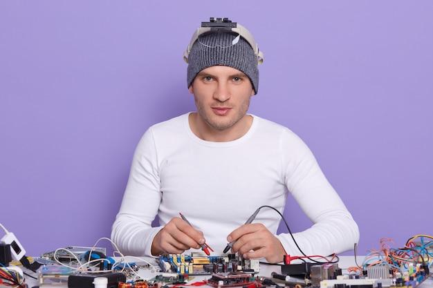 白人の若い男のドレスホワイトシャートとグレーキャップ、デジタル電子エンジニアのワークショップでコンピューターのマザーボードを修復
