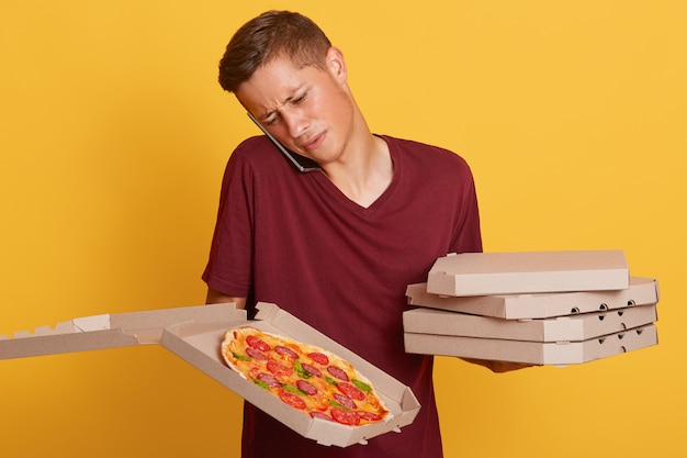 クライアントと電話で話している、住所がわからない、問題が発生している、ピザが入った段ボール箱を持っている混乱した勤勉な配達人