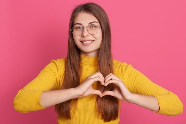 ロマンチックな女性は彼女の手でハートのシンボルを作る黄色のカジュアルシャツをドレスアップ、女性は指で愛のサインを作る