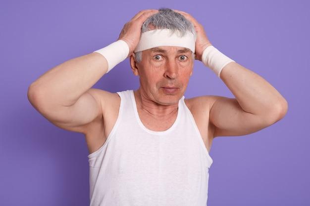 Старший мужчина в замешательстве почесывая голову, надев белую футболку без рукавов, прикасаясь к голове, позирует на сиреневой стене