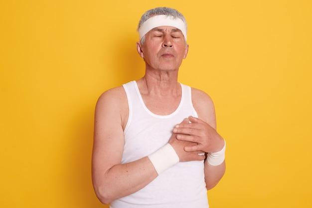 中年の男性が目を閉じてポーズをとって胸に触れ、心臓に痛みを感じ、治療が必要で、スポーツをした後に心臓発作を起こしている