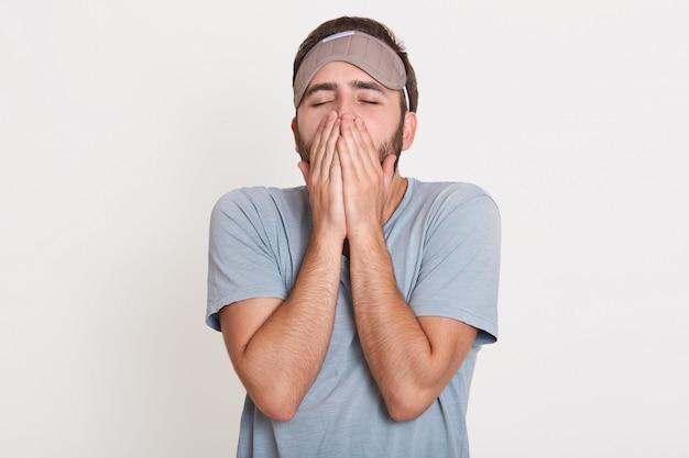 疲れて眠そうなひげを生やした若い男が白い壁に孤立して立って、朝にあくびをして、手で口を覆っています。