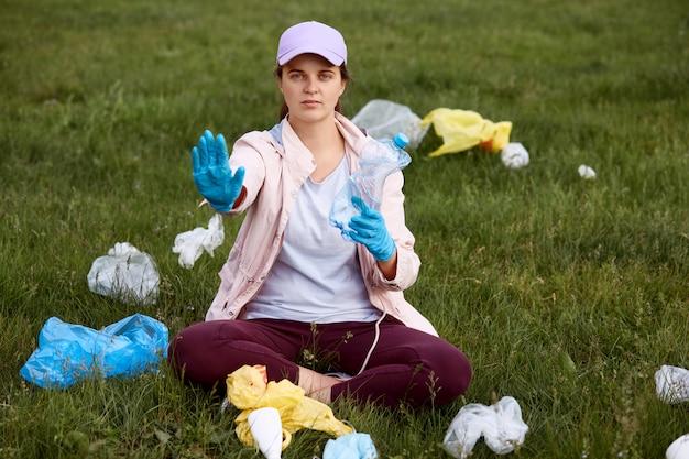 Активист собирает мусор в поле, сидит на зеленой траве и держит пластиковую бутылку