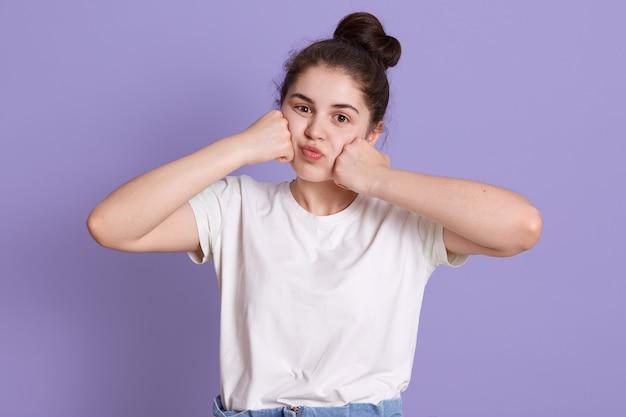Очаровательная молодая леди в белой футболке, держащая кулаки на щеках, позирует в сиреневой стене