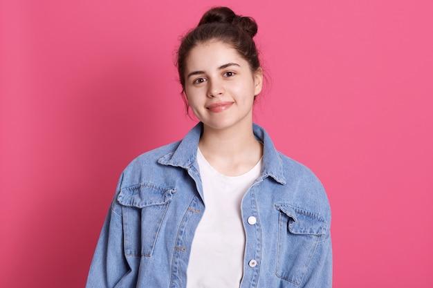 Привлекательная кавказская девушка одевает повседневную джинсовую куртку и белую рубашку, имеет пучок волос