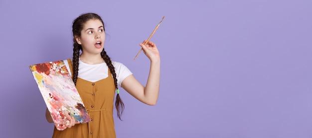 Молодая художница с двумя косичками, держа в руках кисть и палитра