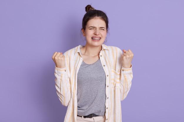 Темноволосая молодая женщина в брекетах сжимает кулаки с сердитым выражением лица