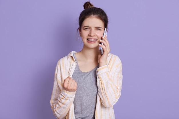 Молодая девушка разговаривает с другом и сжимает кулак