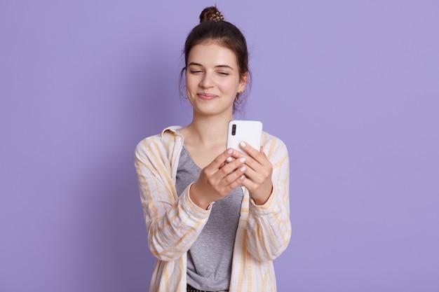 ライラックの壁にポーズカジュアルな服装を着て幸せな笑顔の若い女性