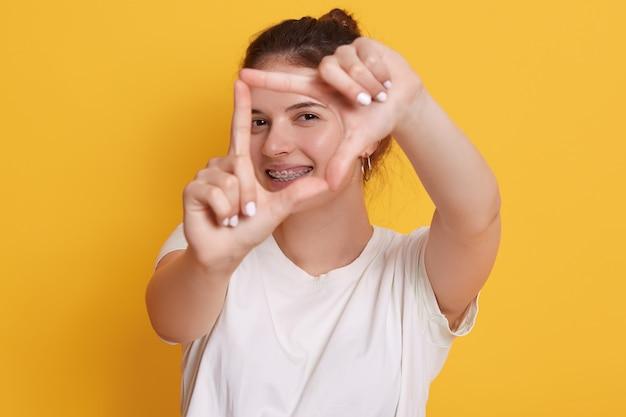 Счастливая усмехаясь молодая женщина делая рамку перед ее лицом и усмехаться