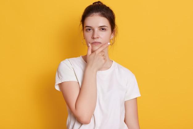 Серьезная молодая молодая женщина в белой футболке
