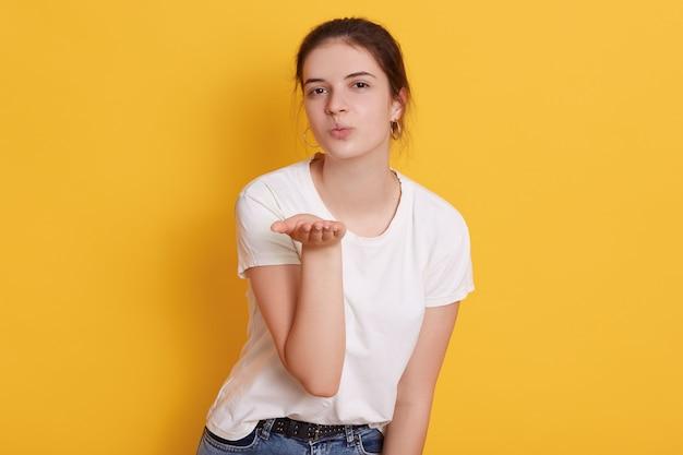 Привлекательная темноволосая молодая женщина одевает белую футболку, дует воздушный поцелуй во время позирования