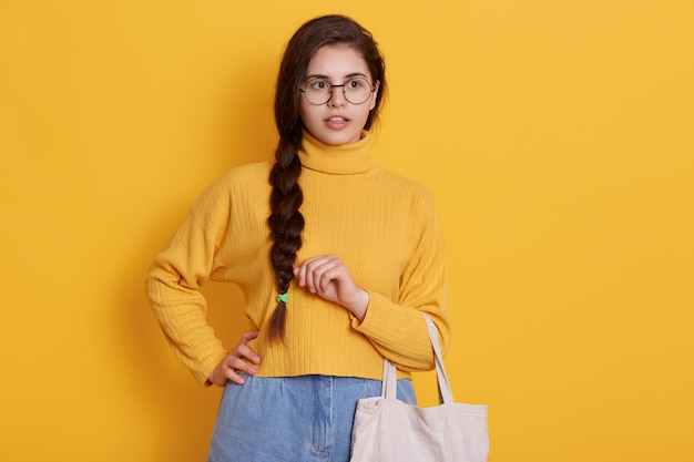 Шокирован молодая женщина, носить повседневную рубашку, держа в руках эко мешок