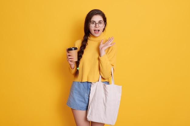Молодая стильная молодая женщина носить рубашку и короткие, дама держит сумку и забрать кофе