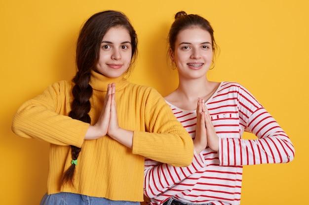 Две молодые девушки в повседневных рубашках позируют ладонями и улыбаются