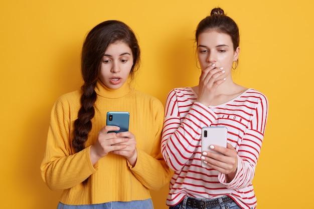 Две подружки держат в руках телефоны и смотрят на экраны большими глазами