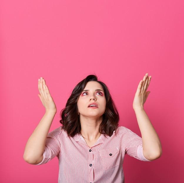 手のひらを上げて見上げる何かについて訴えかけるような黒髪の若い女性は、バラ色の背景の上に孤立しています。待望の物乞いをする女性。