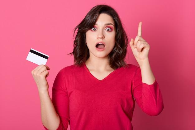 信じられない思いで驚いた若いきれいな女性、人差し指で上を向き、クレジットカードと信じられないほど広く開いた口、驚いた表情の女性。