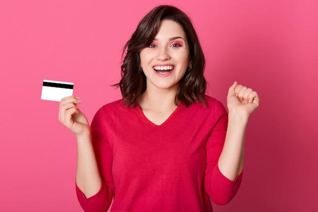 幸せな表情で叫び、握りこぶしを握り締めて、成功を祝って、クレジットカードを持っている、赤いカジュアルシャツを着て、バラ色の壁に立っている若いブルネットの女性。
