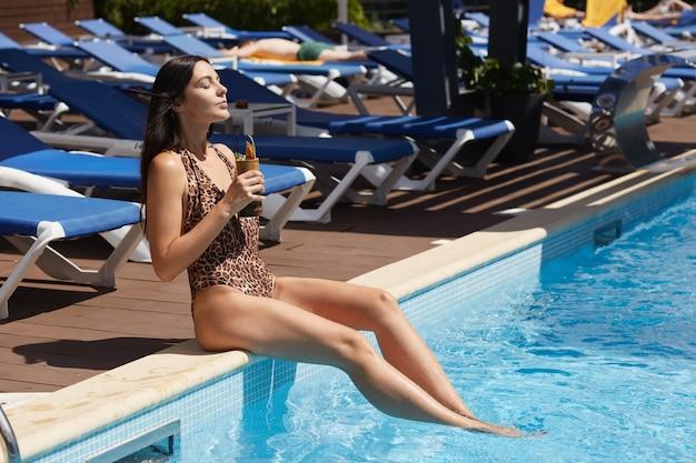 ヒョウ柄のスタイリッシュな水着を着て、プールサイドに座って新鮮なカクテルを楽しんでリラックスできる女性