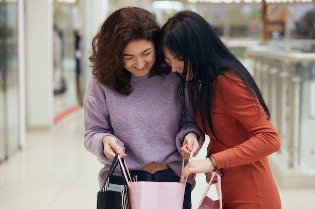 Две темноволосые дамы смотрят в сумку с покупками на новую одежду, девушки в свитерах, позируют в торговом центре после покупки новых платьев, женщины выглядят счастливыми.