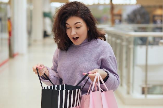 開いたショッピングバッグの内側を見て、余計なものを見ているブルネットの少女は、嬉しそうに驚いて、口を開けて立っていて、驚きました。