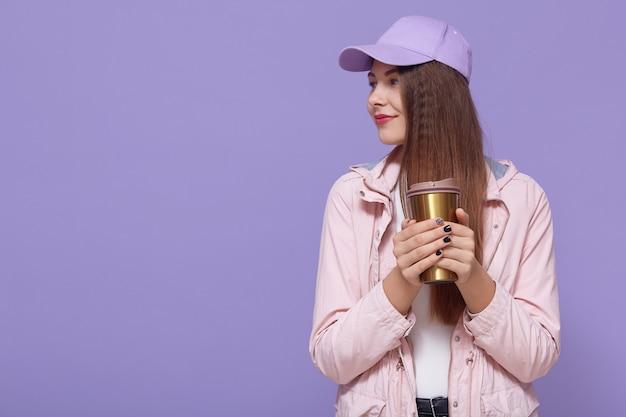 野球帽を身に着けている思いやりのある女性の肖像画は、魔法瓶からコーヒーを飲む