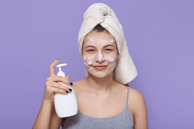 洗浄手ゲルポンプディスペンサーを保持している女性、泡を洗うとポーズし、白いタオルで包まれています。