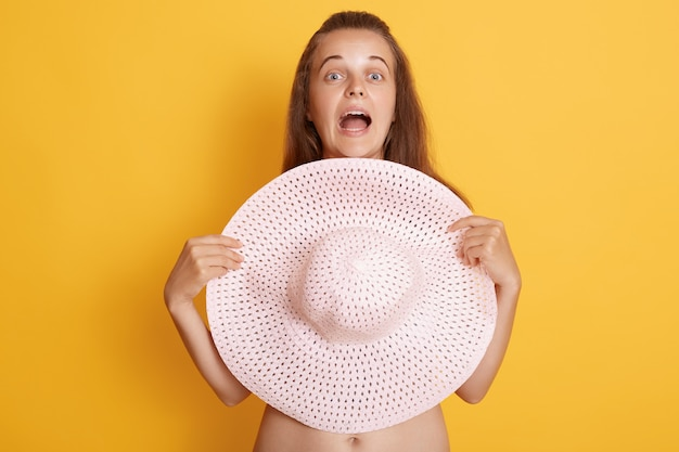 口を大きく開けて麦わら帽子で彼女の胸を覆っているびっくりした若い女性のクローズアップ表示