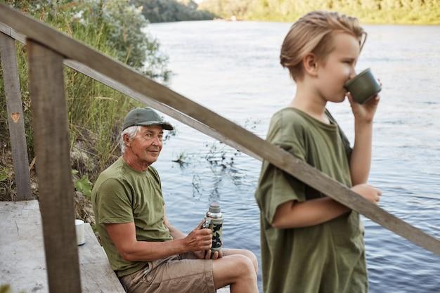 Внук и дедушка ловят рыбу на реке