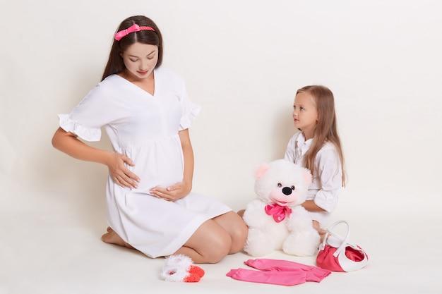 Беременная мать и дочь весело вместе