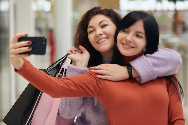 ショッピングモールで「自分撮り」を取る買い物袋を持つ美しい女の子