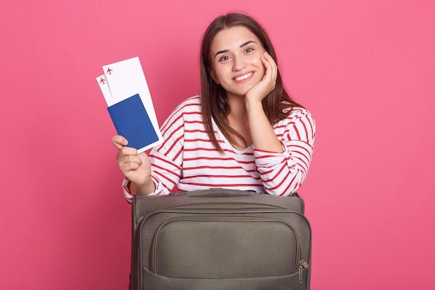 スーツケースでポーズのチケットでパスポートを保持している女性旅行者を笑顔
