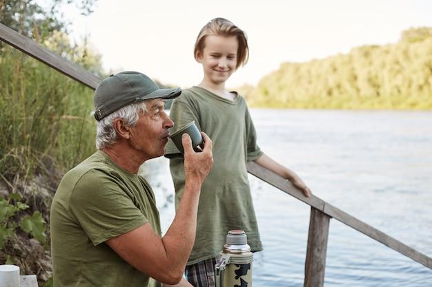 Рыболовство отца и сына на береге реки или озера, чай старшего человека выпивая от термоса, семья представляя на деревянных лестницах водя к воде, отдыхает на красивой природе.