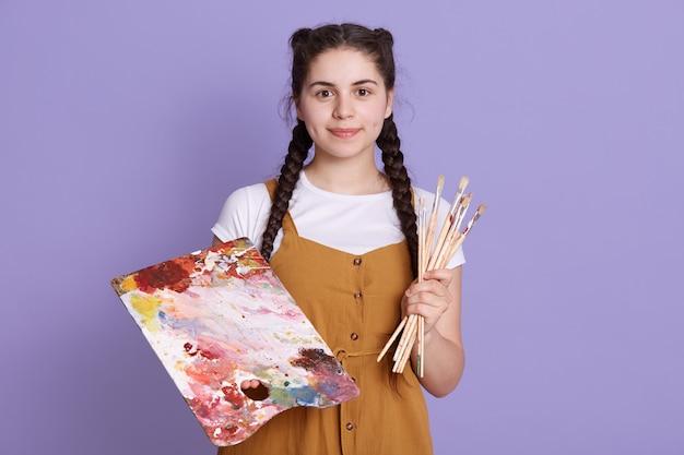 カジュアルな服装を着て、ライラックの壁の上に孤立して立っている美しい水彩画の花のデザインを作成する才能のある女性。